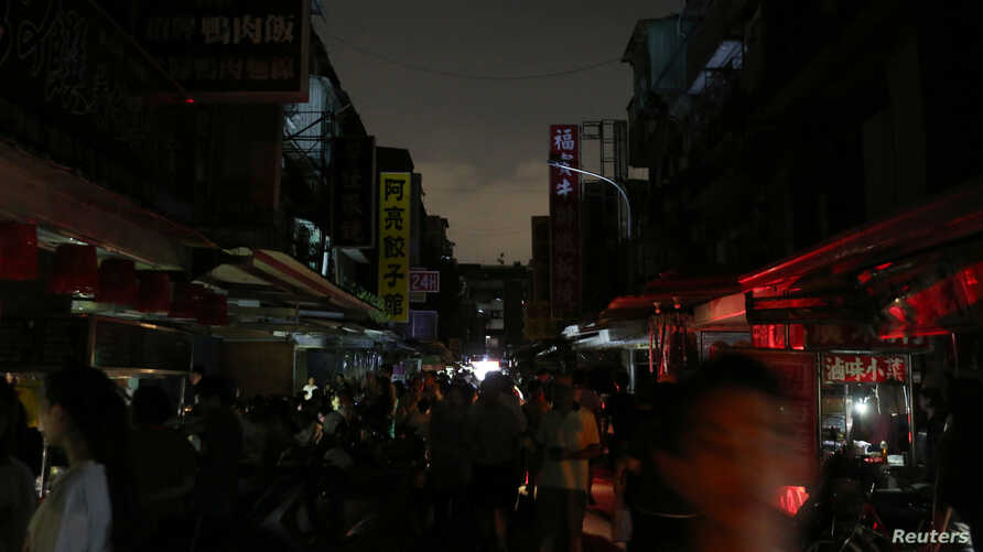 People walk on a street during a massive power outage in Taipei, Taiwan, Aug. 15, 2017. The power was out for hours in a sweltering heat.