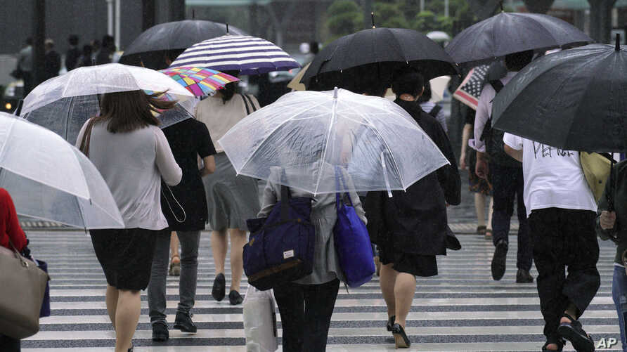 FILE - Pedestrians cross a road in the wind and rain as Typhoon Shanshan approaches, Aug. 8, 2018, in Tokyo. Western Japan is bracing for Typhoon Cimaron, which could bring 800mm (32 inches) of rain to Shikoku.