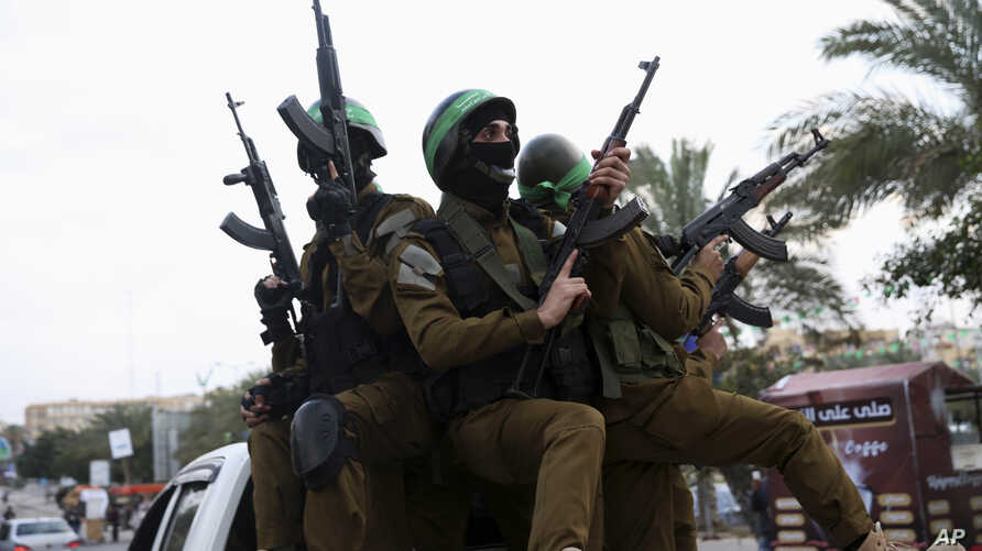 FILE - Masked militants from a military wing of Hamas hold their rifles in Gaza City, Dec. 13, 2017.