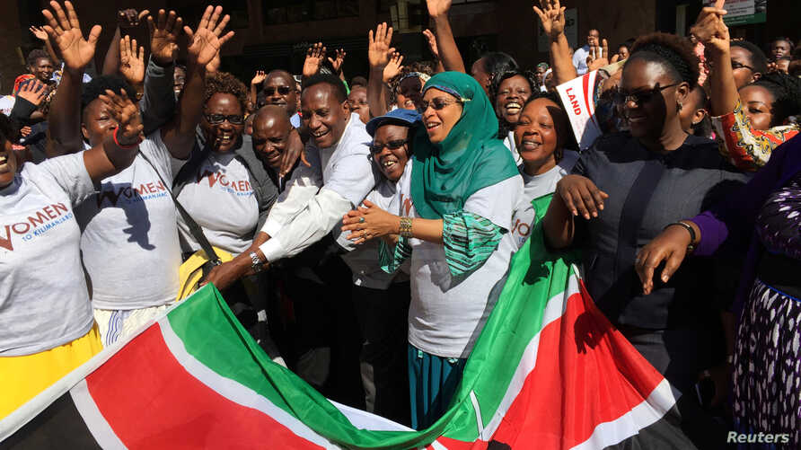 On Oct. 13, 2016, Kenya's Lands Minister Jacob Kaimenyi (5th L) and Mariamu El Maawy (7th L), principal secretary in the Lands and Physical Planning Ministry, stand with women who planned to climb Mount Kilimanjaro as part of a campaign for land righ