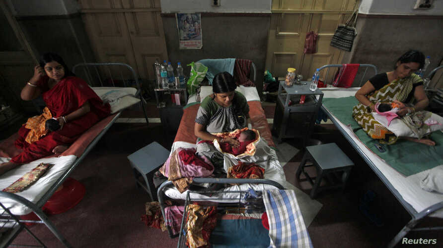 FILE - Mothers hold their newborn babies as they rest inside a maternity hospital, in Kolkata, July 11, 2012.