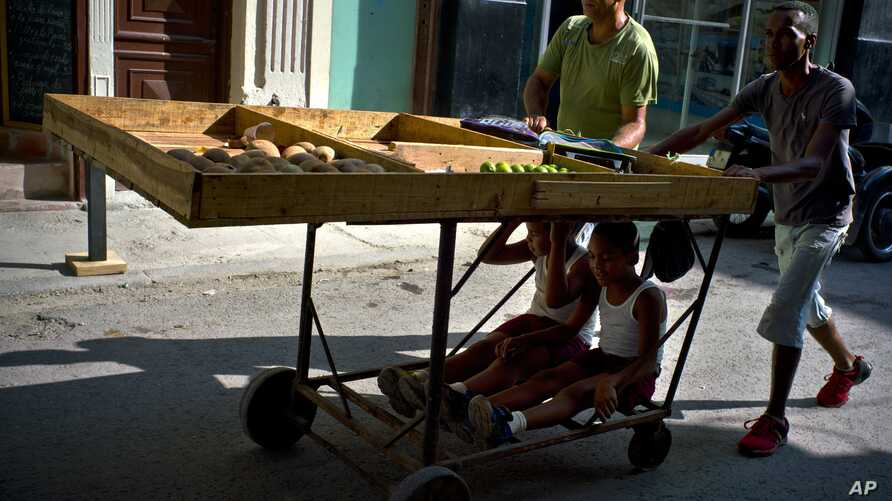 Fruit and vegetable vendors push their cart after a day's work, as two boys ride under the cart in Havana, Cuba, Wednesday, May 31, 2017.  The number of officially self-employed Cubans has grown by a factor of five since President Raul Castro launche