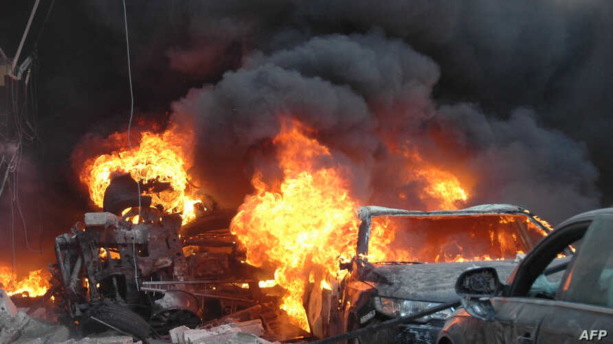 Flames engulf a vehicle following a car bomb along  al-Khudary Street in the Karm al-Loz neighborhood in the central Syrian city of Homs on April 9, 2014.