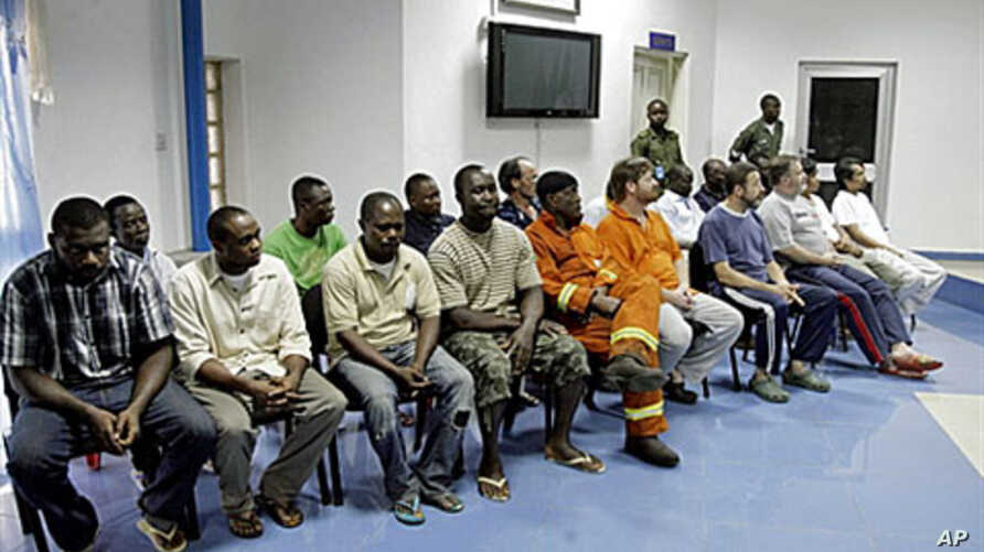 The 19 nineteen oil and construction workers taken hostage by Niger Delta militants and freed last week sit together in Port Harcourt, 18 Nov 2010