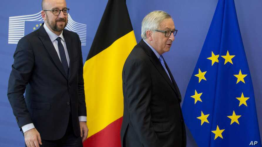 Belgian Prime Minister Charles Michel (L) walks European Commission President Jean-Claude Juncker prior to a meeting at EU headquarters in Brussels on March 16, 2018.