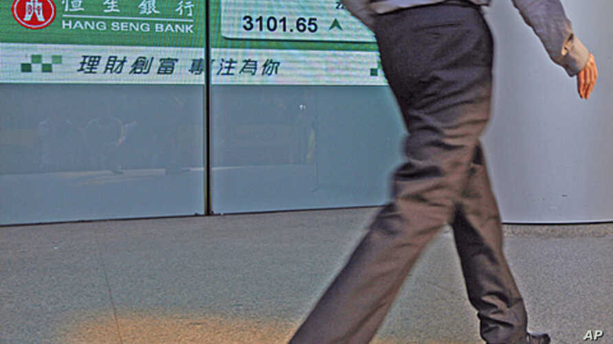A man walks past a panel displaying the Hang Seng index trend at the end of the trading day at the Hong Kong Stock Exchange, July 22, 2011
