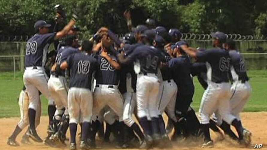 Young baseball players celebrate an extra-innings victory at a sports academy run by the Tampa Bay Rays in Venezuela