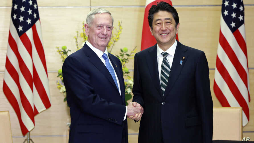 U.S. Defense Secretary Jim Mattis, left, and Japanese Prime Minister Shinzo Abe, right, shake hands at the prime minister's office in Tokyo, Feb. 3, 2017.