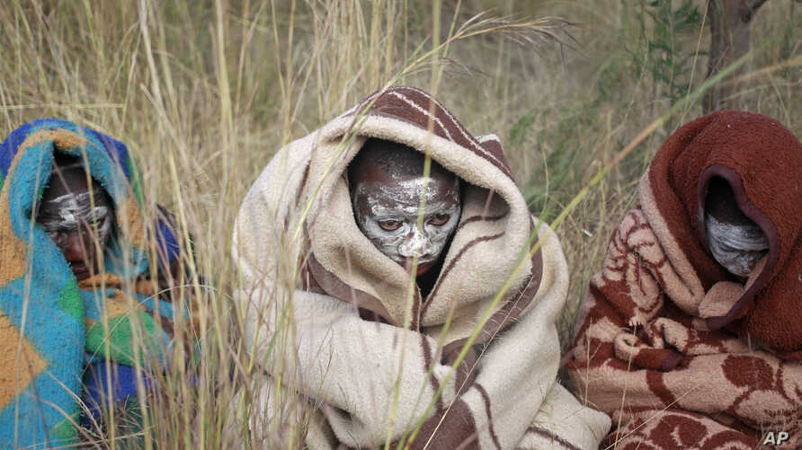 South African boys covered with a blankets and smeared with chalky mud sit in a field as they undergo a traditional male circumcision ceremony into manhood in Qunu, South Africa, June 30, 2013.