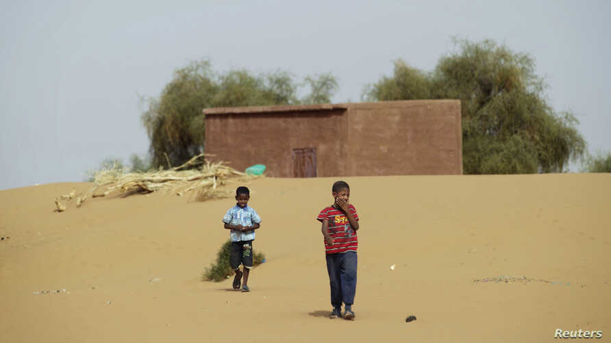 Boys walk on desert sands in the town of Moghtar-Lajjar in west Africa's Sahel region, where the United Nations says civil unrest and a drought  have put 18 million people in food insecurity, May 25 2012.
