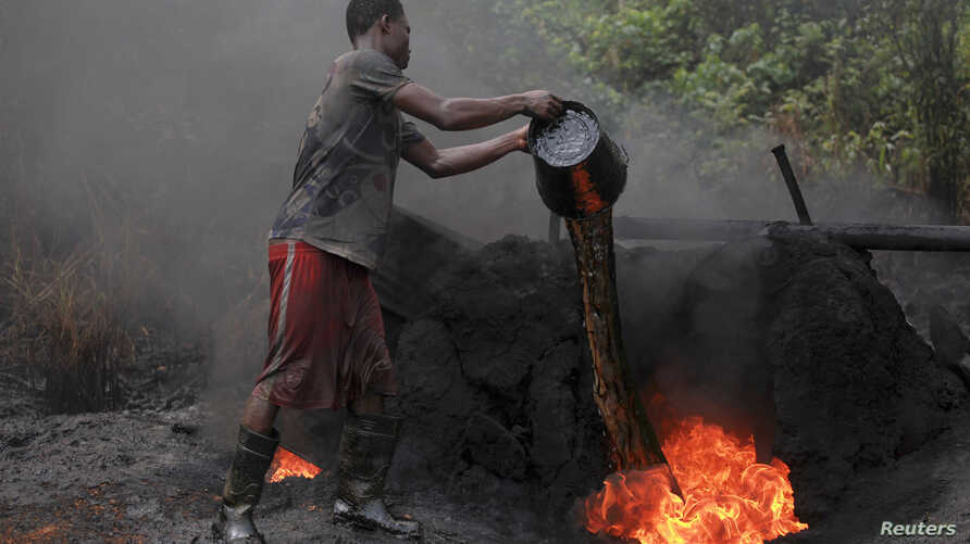 A man working at an illegal oil refinery site pours oil under a locally made burner to keep the fire going, near river Nun in Nigeria's oil state of Bayelsa November 27, 2012.