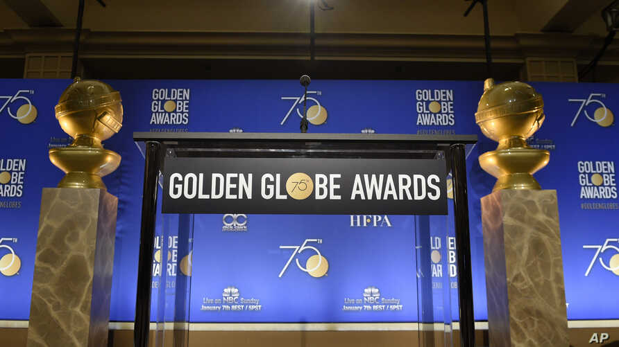 Two Golden Globes statues flank the podium prior to the nominations for 75th annual Golden Globe Awards at the Beverly Hilton hotel in Beverly Hills, Calif., Dec. 11, 2017.
