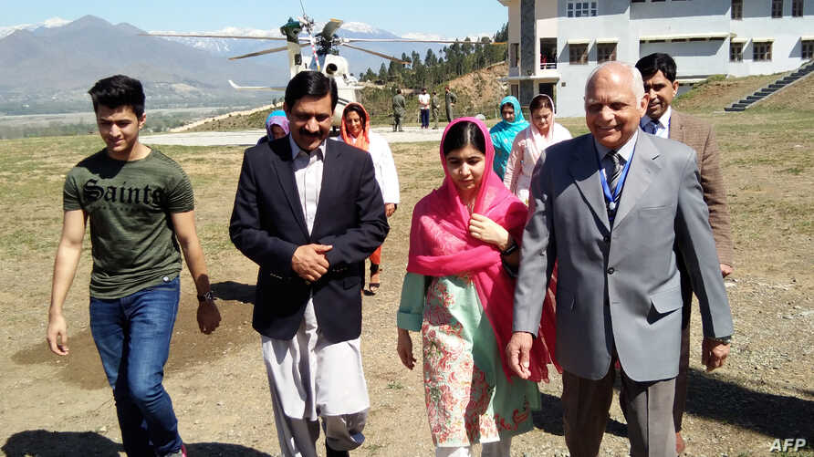 Pakistani activist and Nobel Peace Prize laureate Malala Yousafzai, center, arrives along with her father Ziauddin Yousafzai, second left, brother Atal Yousafzai, left, and the principal of all-boys Swat Cadet College Guli Bagh, during her hometown v