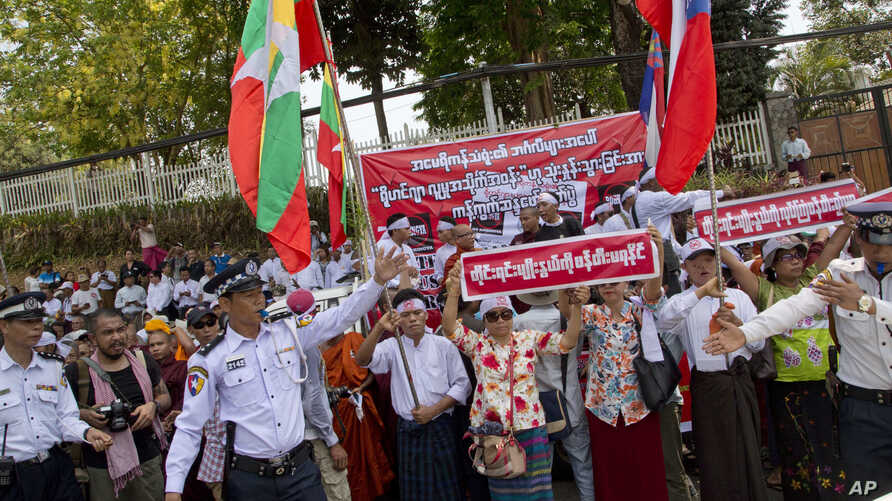 """Police officers try to direct traffic as members of a Buddhist nationalist group protesting outside the U.S. Embassy in Yangon, Myanmar against the embassy's April 20, 2016 statement with the word """"Rohingya"""" Thursday, April 28, 2016. Myanmar national"""