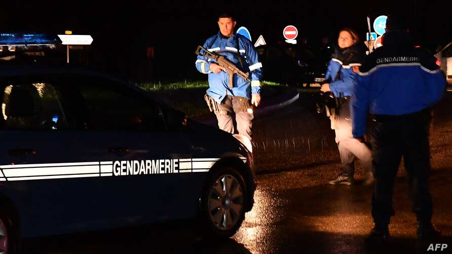 Gendarmes stand guard on a road near a retirement home for monks in Montferrier-sur-Lez, southern France, early on Nov. 25, 2016, after an armed man burst into the home, killing a woman.