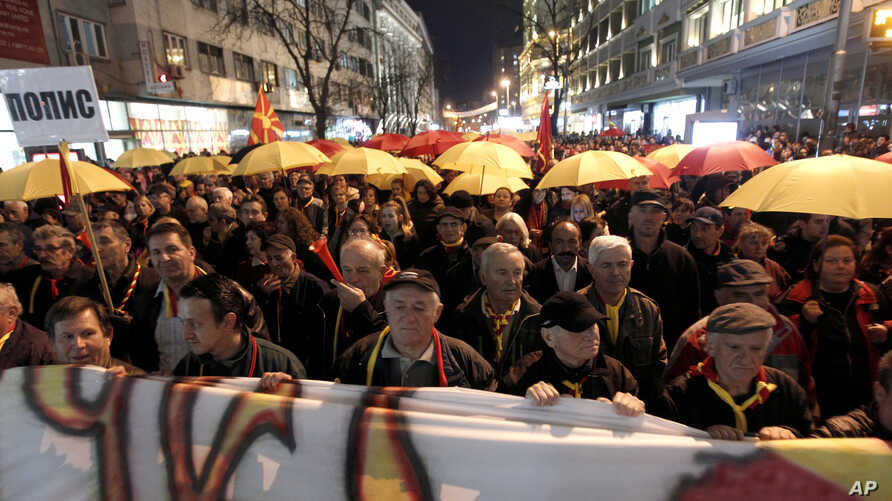 Protesters carrying umbrellas in colors of the national flag march through a street in Skopje, Macedonia, March 10, 2017. Thousands of Macedonians have been protesting against the designation of Albanian as a second official language nationwide.
