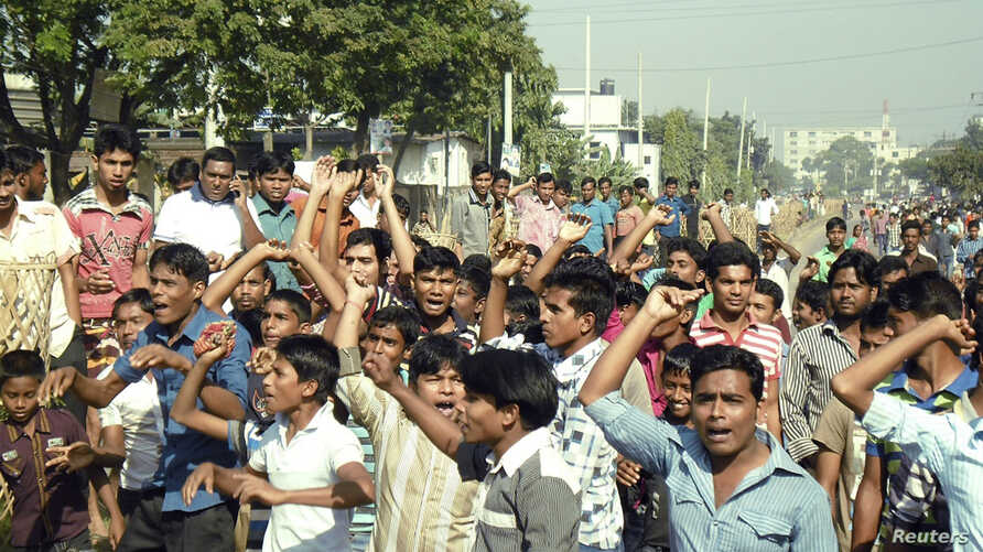 Garment workers shout slogans as they block a street during a protest demanding higher wages in Gazipur, Nov. 13, 2013.