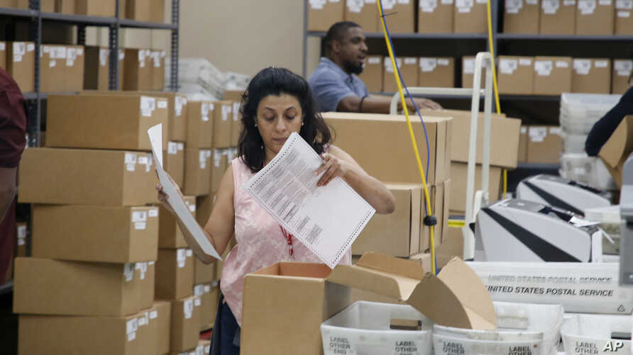 A Broward County Supervisor of Elections worker looks at a ballot during a canvasing board meeting, Nov. 9, 2018, in Lauderhill, Fla.