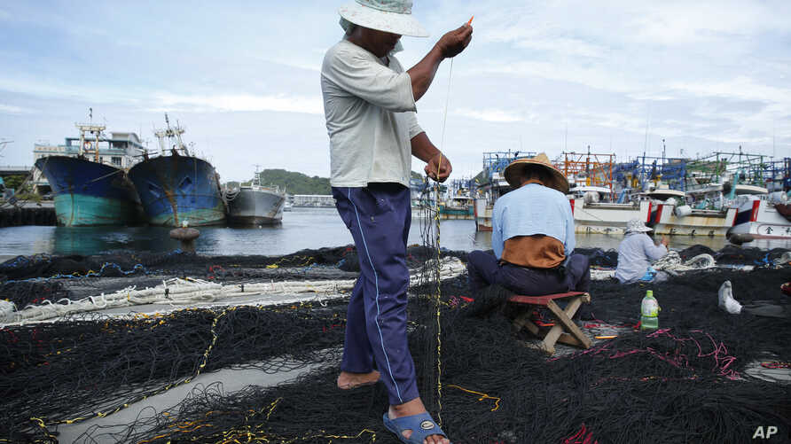 As Typhoon Soudelor approaches, fishermen make use of time in port to repair nets in Yilan County, northeastern Taiwan, Thursday, Aug. 6, 2015.