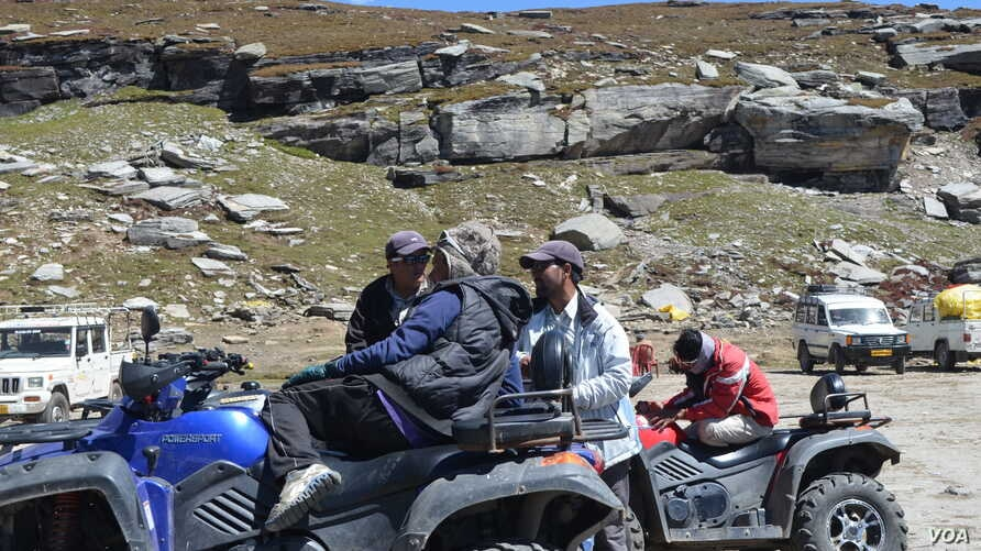 People sit on their all terrain vehicles at Rohtang Pass, India, Sept. 20, 2013. (Anjana Pasricha for VOA)