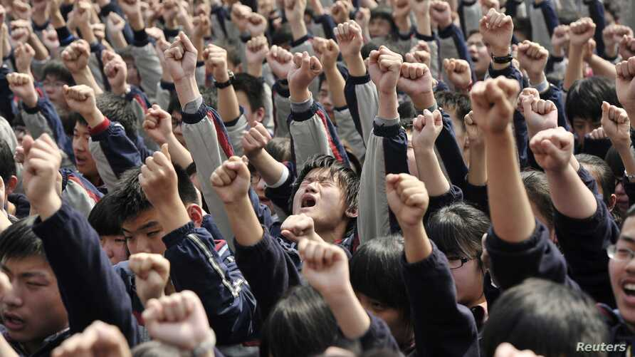 """FILE - Students yell slogans such as """"I must go to college"""" and """"Father and mother, I love you"""" following the instructions of a lecturer during a speech at a high school in Nanjing, Jiangsu province March 28, 2012. The speech aims to boost the morale"""