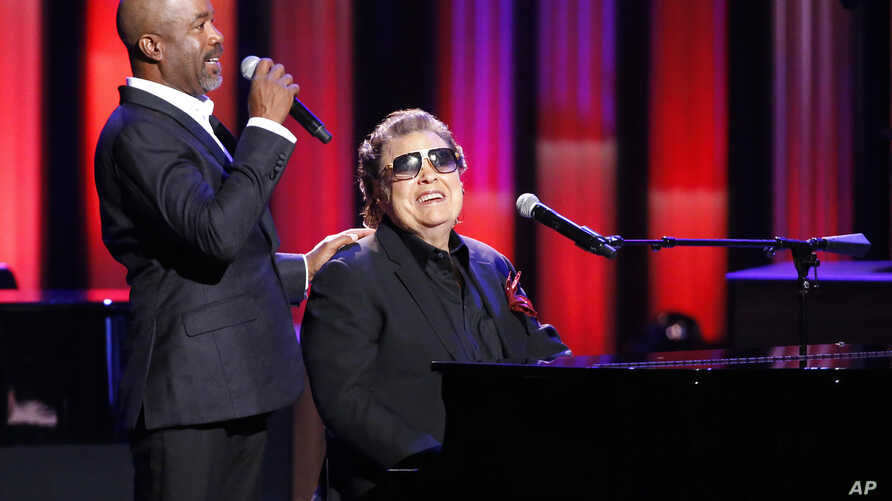 """In this Oct. 8, 2018, photo, host Darius Rucker, left, introduces Ronnie Milsap during """"An Opry Salute to Ray Charles"""" at the Grand Ole Opry House in Nashville, Tenn."""