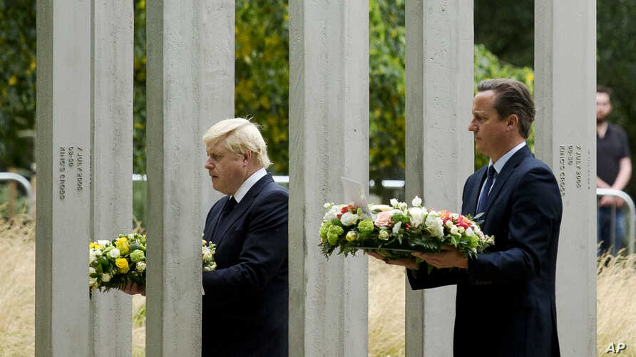 Britain's Prime Minister David Cameron, right, and London Mayor Boris Johnson walk through the 7/7 memorial in Hyde Park to lay wreaths in London, Tuesday, July 7, 2015.