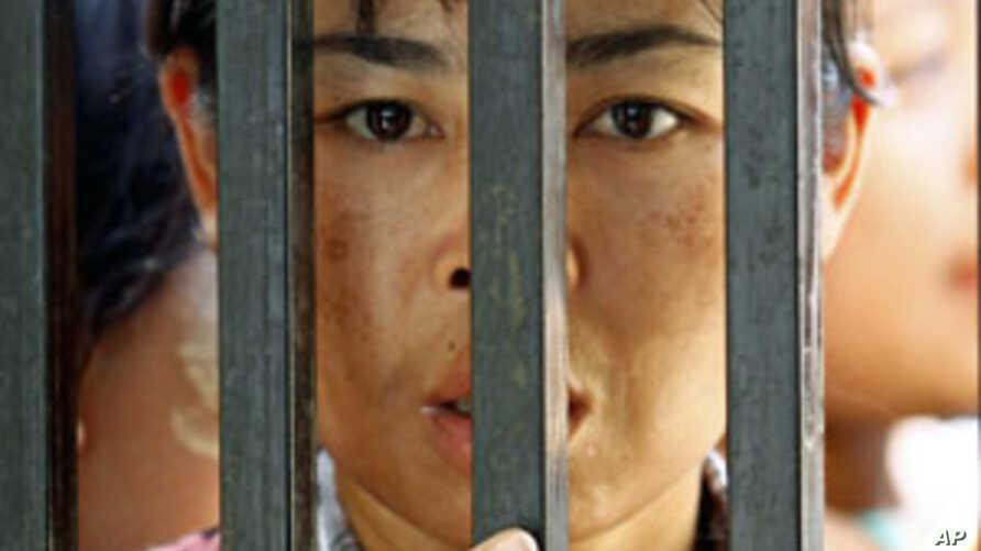 Family members of prisoners wait for their release in front of the Insein Prison gate in Yangon. Myanmar's new government began freeing about 14,000 prisoners and commuting thousands more sentences on Tuesday in an amnesty critics dismissed as a toke