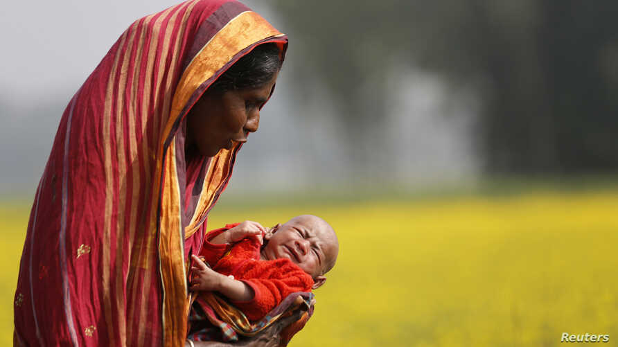 Monowara holds her 22-day-old grandson Arafat, as she walks through a mustard field on the outskirts of Dhaka, Bangaldesh, Jan. 22, 2014.