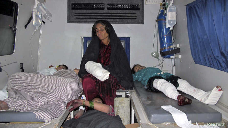Injured Afghan civilians rest in an ambulance as they are brought to a hospital in Helmand province, December 31, 2014.
