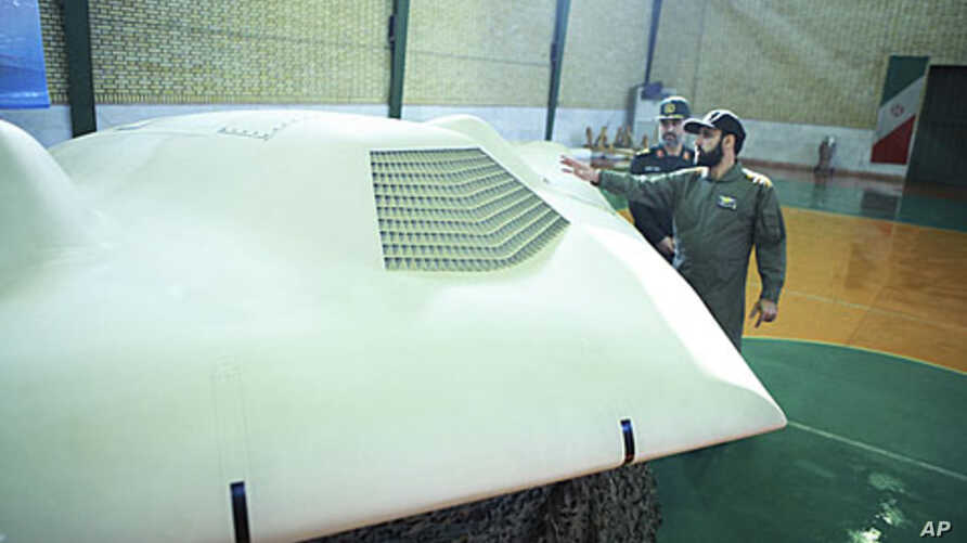 An undated picture received by Reuters December 8, 2011, allegedly shows members of Iran's revolutionary guard standing next to the captured US drone.