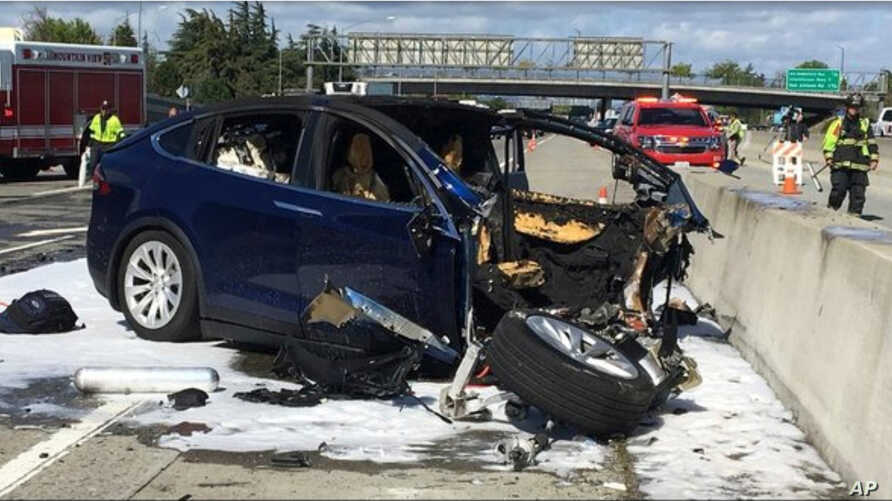 FILE - In this March 23, 2018, photo provided by KTVU, emergency personnel work a the scene where a Tesla electric SUV crashed into a barrier on U.S. Highway 101 in Mountain View, Calif. Tesla said on March 31, that the vehicle was operating on Autop