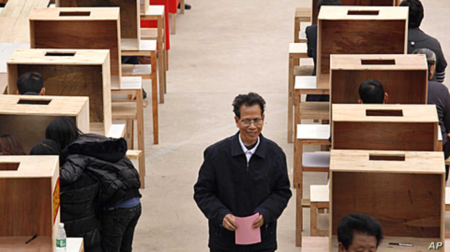 Lin Zuluan holds his ballot before casting during an election to select village committees in which he was elected to village chief in Wukan, Lufeng city, south China's Guangdong province, March 3, 2012.
