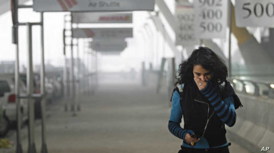 A girl tries to protect herself from the smoke coming from one of the parking lots of Madrid's Barajas airport after a car bomb explosion, which injured four people, December 30, 2006 (file photo)