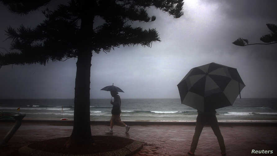 FILE -  Pedestrians holding umbrellas walk on the footpath above Manly Beach during rainfall on an autumn day in Sydney. Three-quarters of the trash found off Australian beaches is plastic, study says.