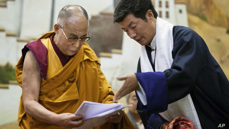 Lobsang Sangay, prime minister of the Tibetan government-in-exile, right, presents a document to spiritual leader the Dalai Lama at the Tibetan Children's Village School in Dharmsala, India, June 5, 2014.