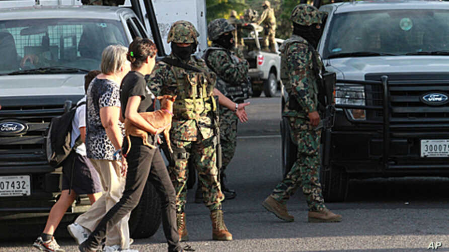 Two women walk next to members of Mexican Navy in Boca del Rio, Veracruz State. Another 32 bodies have been found in three homes in Mexico's eastern state of Veracruz, where dozens of corpses were dumped on a road in broad daylight last month, the na
