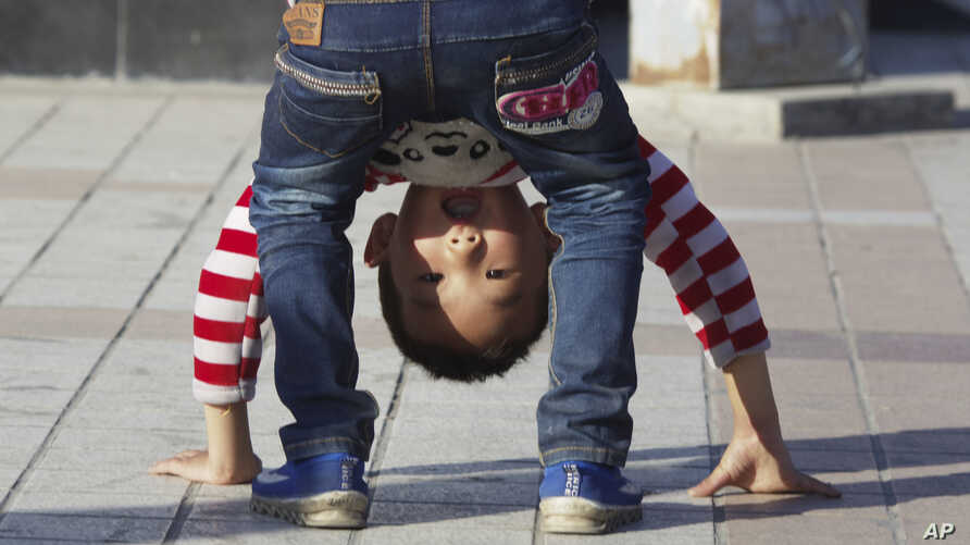 FILE - A child bends over in a public park in Yinchuan in northwestern China's Ningxia Hui autonomous region, Oct. 8, 2015. China this week officially ended its three-decade old one-child policy.