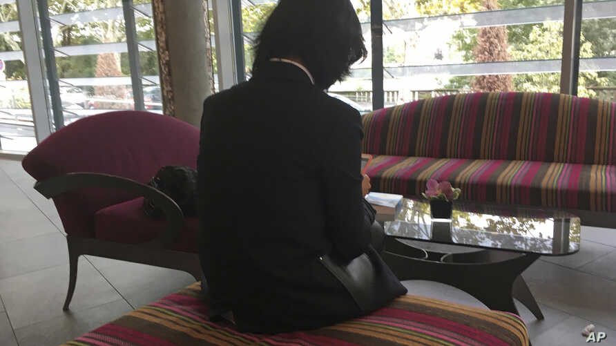 Grace Meng, the wife of missing Interpol President Meng Hongwei, who does not want her face shown, consults her mobile phone in the lobby of a hotel in Lyon, central France, where the police agency is based, on Oct. 7, 2018.