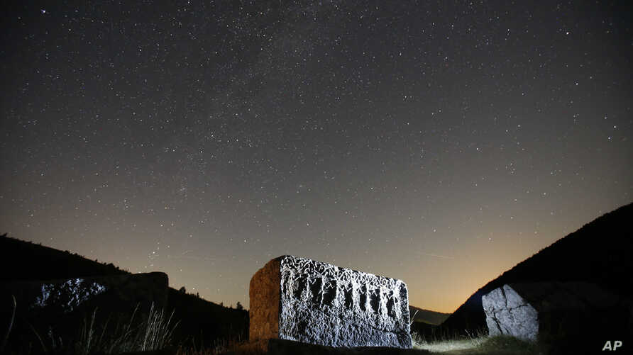 Stars and meteor streaks, near the line of horizon, are seen behind a medieval tombstone believed to be built in the  12th century depicting the ancient ritual dance, near the village of Umoljani, 50 kilometers (31 miles) southeast of Sarajevo, Bosni