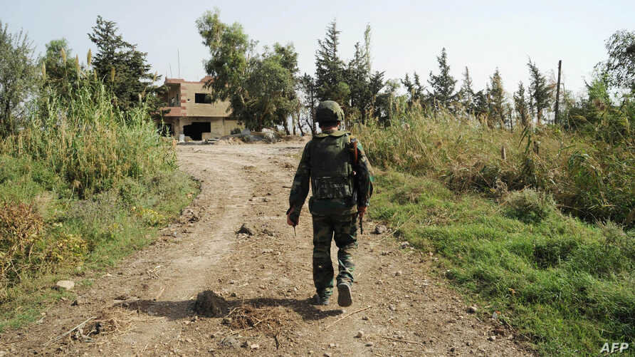 A handout picture released by the official Syrian Arab News Agency (SANA) shows a Syrian soldier walking in a road in the northwestern countryside of Hama on October 15, 2015.