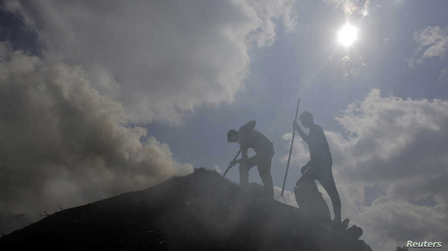 FILE - Palestinian workers rake a pile of wood as they make charcoal for sale, in the West Bank village of Yabad near Jenin, June 11, 2014.