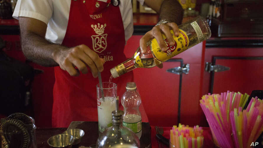 FILE - A bartender pours Cuban Havana Club rum as he prepares a mojito at the Floridita bar in Havana, June 8, 2016. Two liquor giants are escalating a 20-year fight to secure the rights to sell Havana Club rum in the United States when the Cuban emb