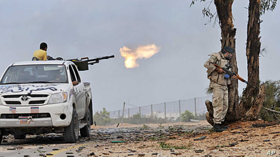 Libyan revolutionary fighters fire with a machine gun while attacking pro-Gadhafi forces at the Ouagadougou conference center of Sirte, Libya, October 7, 2011.