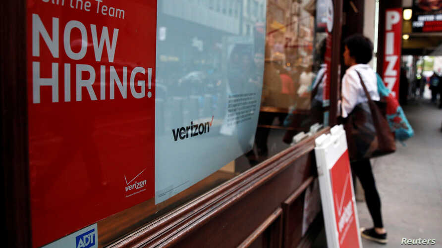 """A """"Now Hiring"""" sign is posted on a Verizon store in Manhattan in New York City, May 10, 2016."""