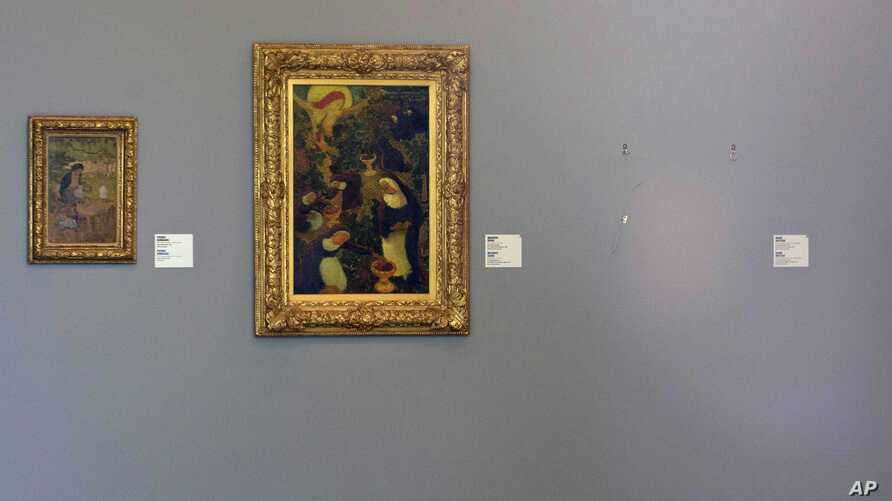 """The empty space where Henri Matisse' painting """"La Liseuse en Blanc et Jaune"""" was hanging, right, is seen next to a painting by Maurice Denis, center, and Pierre Bonnard, left, at Kunsthal museum in Rotterdam, Netherlands, Oct. 16, 2012."""
