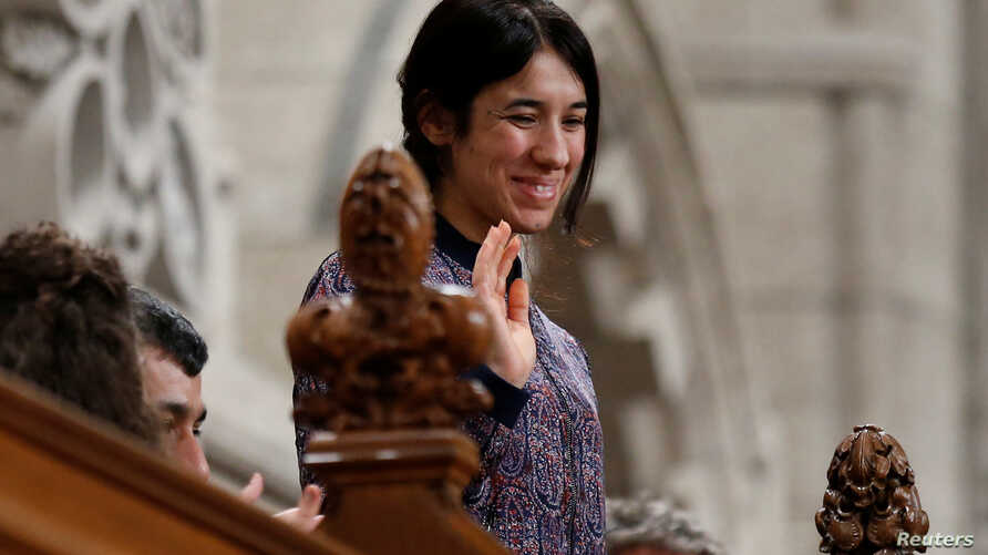 Nadia Murad Basee Taha, U.N. Goodwill Ambassador for the Dignity of Survivors of Human Trafficking, waves while being recognized by the speaker in the House of Commons on Parliament Hill in Ottawa, Ontario, Oct. 25, 2016.