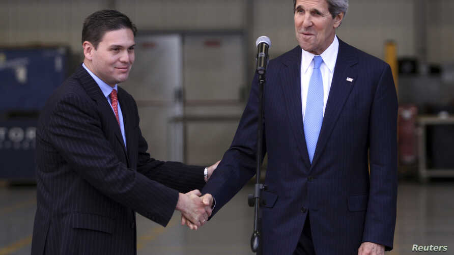 Colombia's Defense Minister Juan Carlos Pinzon (L) shakes hands with U.S. Secretary of State John Kerry during a visit to the anti-narcotics department in Bogota, August 12, 2013.
