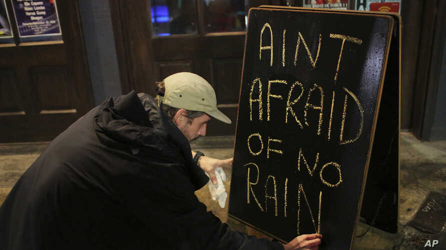 Nick Eberlein, bartender at The Merry Widow, draws a new sign as Tropical Storm Gordon arrives at night, Sept. 4, 2018, in Mobile, Ala. Tropical-force winds from fast-moving Gordon smashed into the coastline of Alabama and the western Florida Panhand