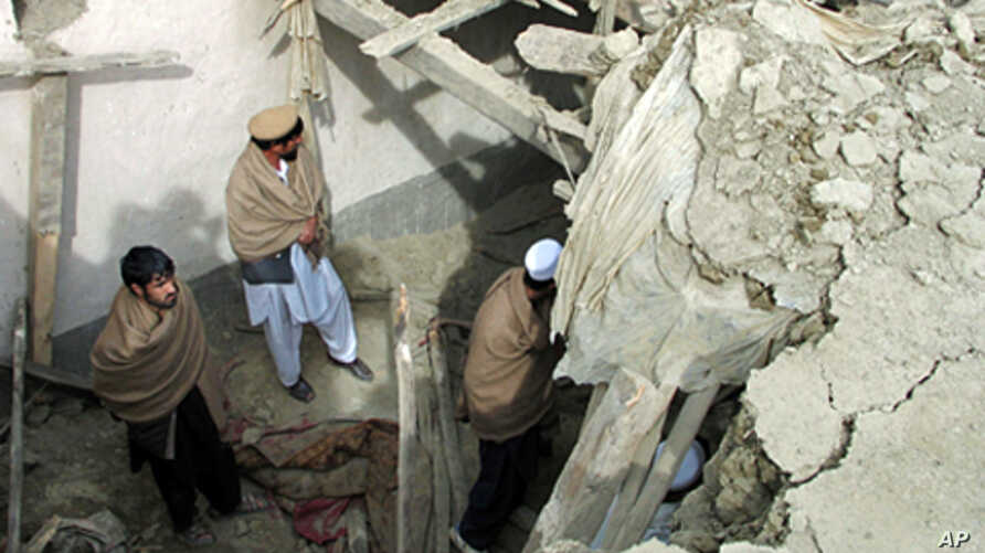 Afghan men stand in the yard of a house that was partly destroyed after an air strike in Nangarhar province, February 21, 2011